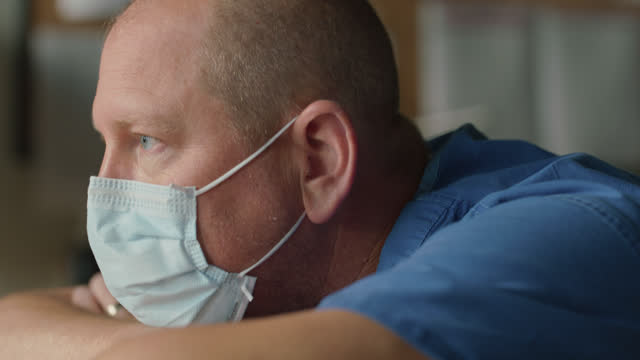 cu contemplative male nurse with head resting on arms removes surgical face mask - epidemic stock videos & royalty-free footage