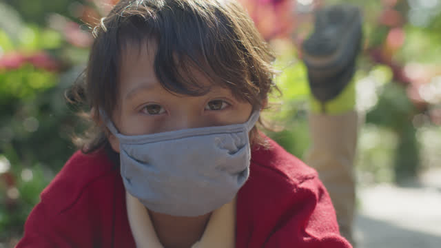 slo mo cu contemplative young boy wearing a face mask looks at camera - one boy only stock videos & royalty-free footage