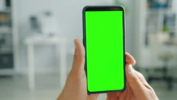 Contemporary smartphone with green screen in male hand on domestic background