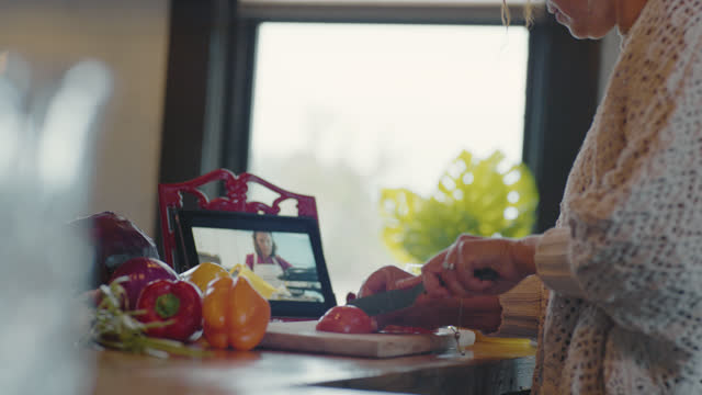 vídeos de stock, filmes e b-roll de contemporary woman slices a tomato as she follows along with a cooking tutorial on her digital tablet - tutorial