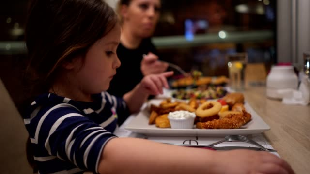 vidéos et rushes de fille de contenu mangeant le dîner dans un restaurant avec sa famille - alimentation lourde