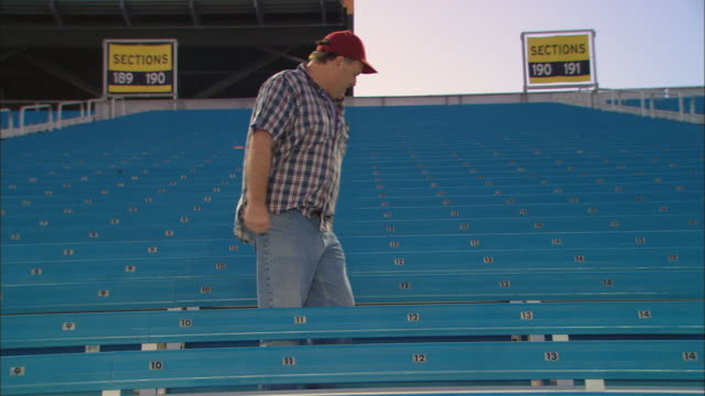 la ws content man sitting down in empty bleachers / homestead, fl, usa - miami dade county stock videos and b-roll footage