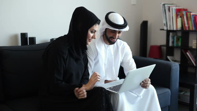 content middle eastern couple viewing photos and videos on laptop - headdress stock videos & royalty-free footage