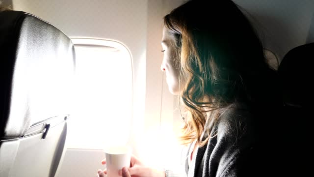 content woman looks out of an airplane woman - vehicle interior stock videos & royalty-free footage