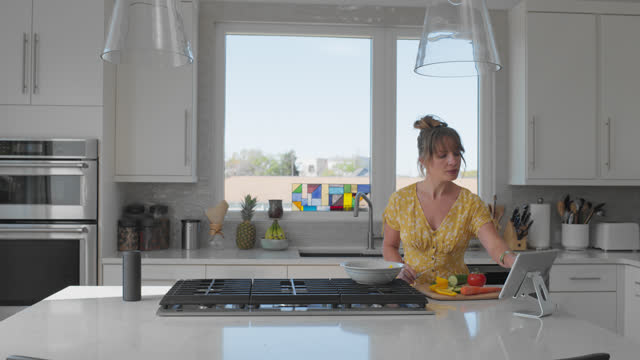 content woman uses a tablet while cooking in her kitchen - 30 34 years stock videos & royalty-free footage