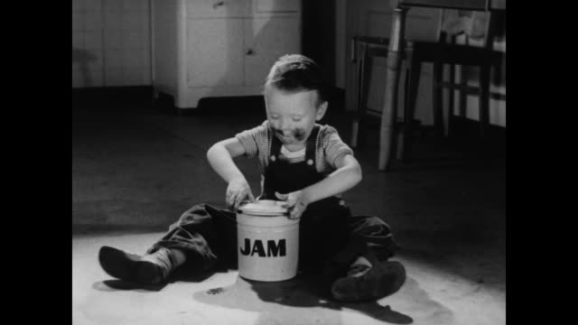 stockvideo's en b-roll-footage met contented boy eats jam on kitchen floor - 1930