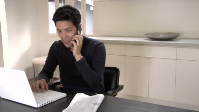 vídeos y material grabado en eventos de stock de ms, contented man using laptop and talking on mobile phone in kitchen - manos detrás de la cabeza