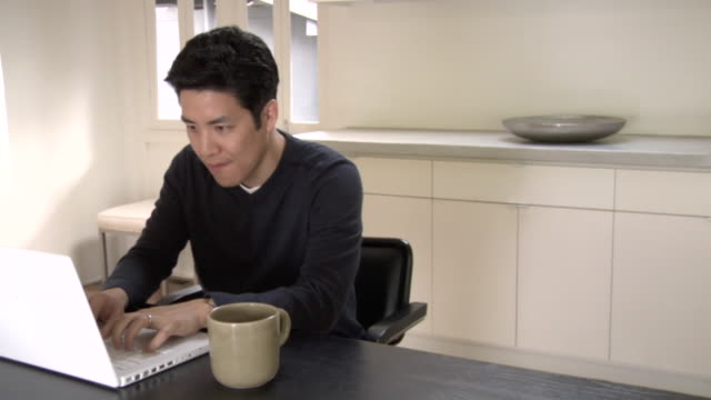 MS, Contented man using laptop in kitchen