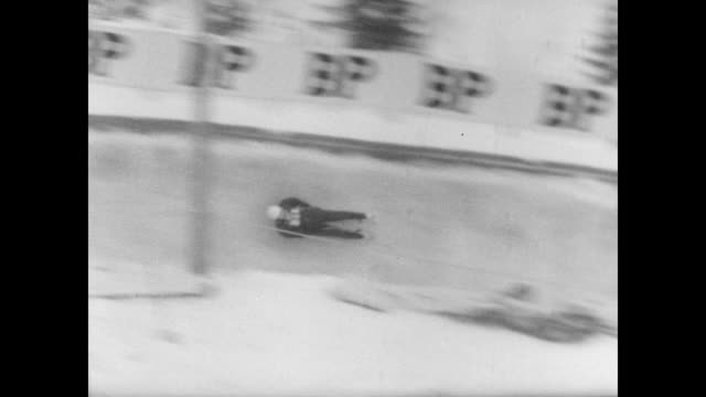 contestant in the world tobogganing championship cleans the runners on his sled / contestant toboggans down the chute track / small crowd watches as... - spielkandidat stock-videos und b-roll-filmmaterial
