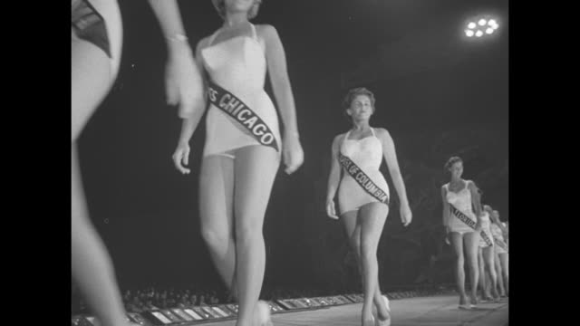 contestants walk on a runway with state sashes bathing suits heels / grace kelly with glasses on and male judge look up / ws miss america 1955 lee... - crutch stock videos & royalty-free footage