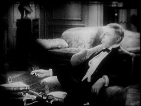 continuation of casual conversation in black tie formal wear between actor walter huston and director dw griffith, conducted in parlor / walter... - 1930点の映像素材/bロール