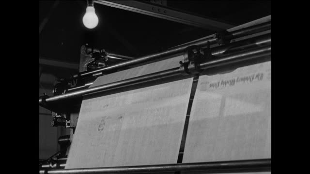 ms continuous rolls of paper move through local newspaper press / rolls turn in press / newsprint runs though press / operator watches press / newspapers move in production line / newspapers drop on to conveyor / hand picks up stack of newspapers - historical reenactment stock videos & royalty-free footage