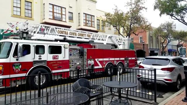 contra costa county fire engine traveling down main street in martinez, california, january 10, 2019. - targa con nome della via video stock e b–roll