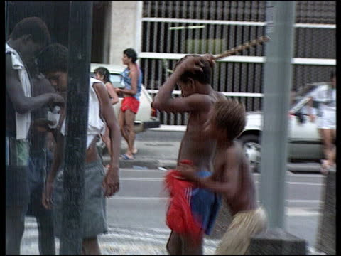 vídeos de stock e filmes b-roll de carey appeal; brazil rio de janeiro lms group of poor black children on streets zoom in starving child on sheet in street zoom in tcms young boy... - esfomeado