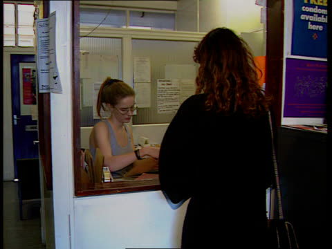 Contraceptive pill ITN LIB London CBV woman along into Brook advisory centre TRACK Woman talking to receptionist as hands over notes Receptionist...