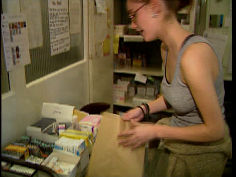 Contraceptive pill ITN LIB London Woman talking to receptionist at Brook Family Planning Centre as hands over notes Receptionist giving woman bag of...