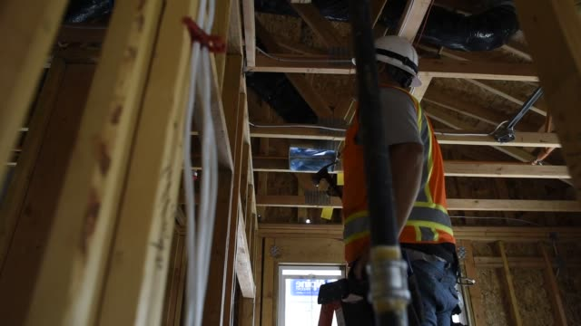 vídeos y material grabado en eventos de stock de contractor installs electrical wiring as he works on a townhouse under construction in the pepper lane development by pulte homes inc in san jose,... - electricista