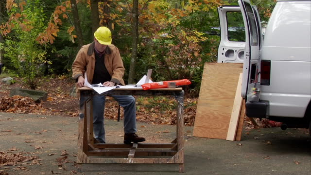 Contractor making notes on workbench on blustery day / homeowner approaching and greeting him / contractor discussing renovation with homeowner