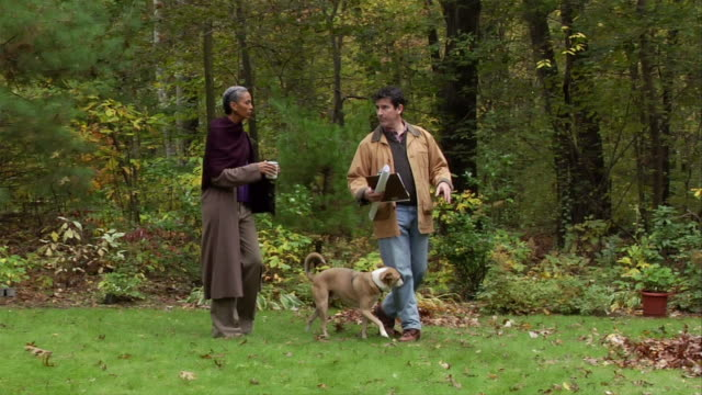 Contractor walking through backyard with homeowner and pet dog to discuss renovation