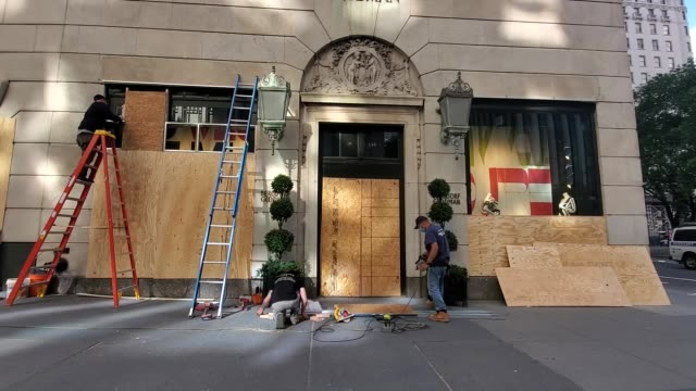 contractors boarding up bergdorf goodman and other store fronts in anticipation for street violence and potential looting as a reaction to the death... - bergdorf goodman stock videos & royalty-free footage