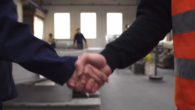 contractors closing a deal with handshake in front of an industrial plant - occupational safety and health stock videos and b-roll footage