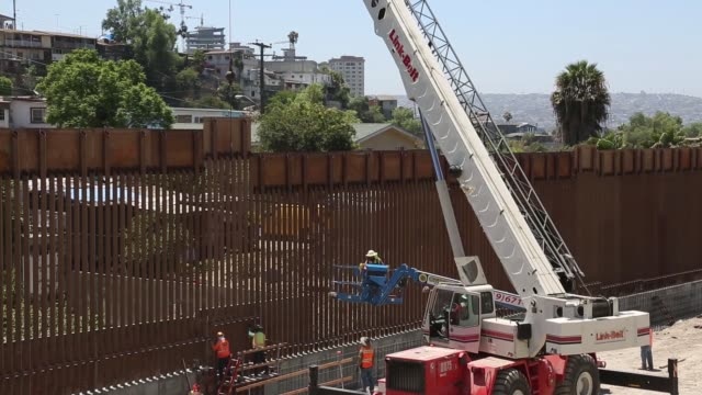 vídeos de stock e filmes b-roll de contractors install the final section of the san diego border wall - divisa