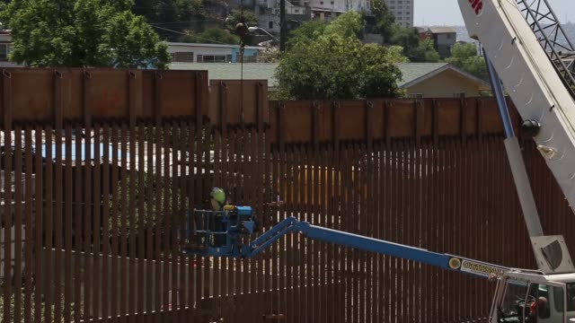 contractors install the final section of the san diego border wall - metal blend stock videos and b-roll footage