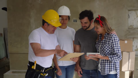 vidéos et rushes de entrepreneurs affichant quelque chose sur le presse-papiers au jeune couple pour une rénovation à la maison et se terminant par une poignée de main tout sourire - reconstruction