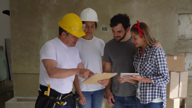 contractors showing something on clipboard to young couple for a home renovation and ending with a handshake all smiling - rebuilding stock videos & royalty-free footage
