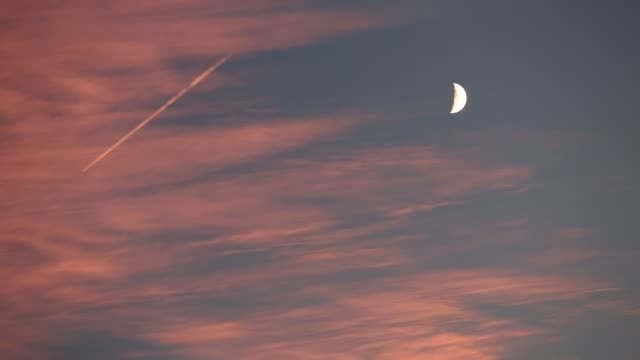 contrails from a plane with a half moon at sunset, ambleside, lake district, uk. - vapour trail stock videos & royalty-free footage