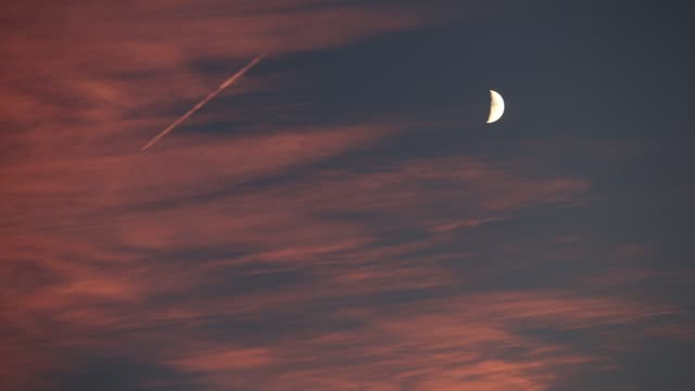contrails from a plane with a half moon at sunset, ambleside, lake district, uk. - half moon stock videos & royalty-free footage