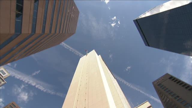 contrails streak the sky above denver skyscrapers. - vapour trail stock videos & royalty-free footage