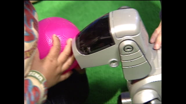 vídeos de stock e filmes b-roll de contributor approval required for all uses children pet aibo robot like a real dog - sony