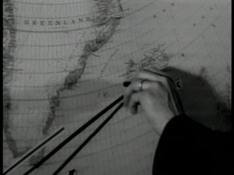 Control operator at table pouring coffee man at wall map CU Hands changing position of model airplane on map turning point at 'Keflavick' Iceland