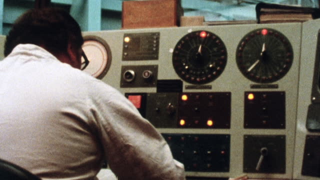 stockvideo's en b-roll-footage met 1981 ds control panel for monitoring nuclear power station with technician on the job / sizewell, england, united kingdom - regelkamer