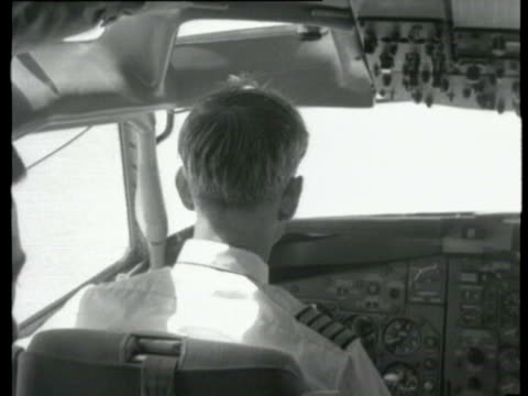 control panels with switches and levers / passengers in seats / passengers chatting / plane wing and engines seen through window / passengers... - 1960 stock-videos und b-roll-filmmaterial