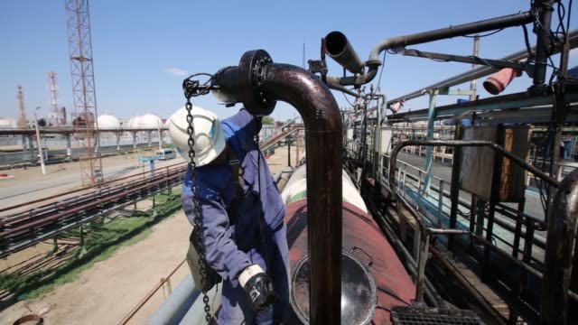 A control room at the Atyrau oil refinery plant operated by KazMunaiGas in Atyrau Kazakhstan July 2 2015 Shots A worker positions a pipe to fill a...