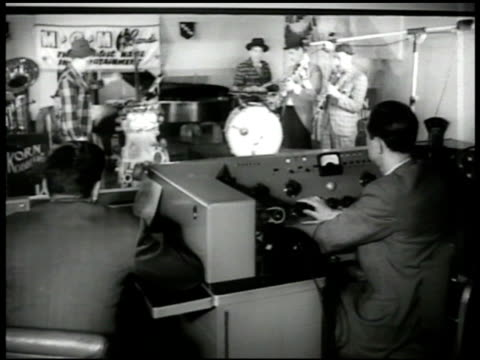 Control room men giving signal on telephone WS Control room men band in recording studio playing Members Charlie Koenig Marty Gold Stan Fritts Howard...
