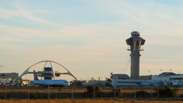 W/S LAX control tower and theme restaurant as Frontier Airbus A319 crosses frame on approach to landing