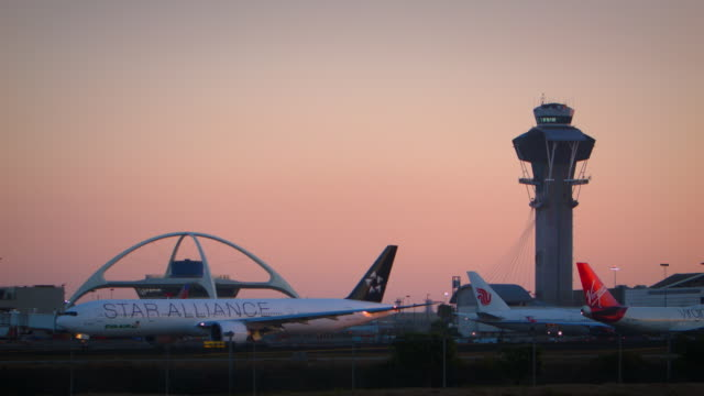 lax control tower and theme restaurant at sunset with star alliance b-777 turning on runway in foreground - air traffic control tower stock videos and b-roll footage