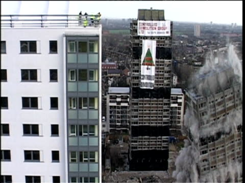 vidéos et rushes de controlled demolition of two tower blocks in east london - imploding