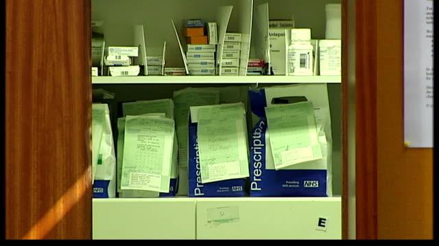 vídeos de stock e filmes b-roll de controversy over plans to replace gp surgeries across london with polyclinics; r14090701 int prescriptions on shelf nurse putting on lightweight... - lightweight