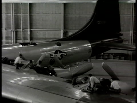 convair b36 peacemaker warehouse factory men working on wing front landing gear near tires of b36 worker walking in front of row of b36 engines... - 1948 stock videos & royalty-free footage