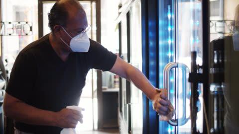vídeos y material grabado en eventos de stock de propietario de la tienda de conveniencia usando mangos de refrigerador de limpieza de máscara durante la pandemia de covid-19 - pequeña empresa