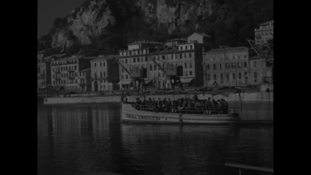 vídeos de stock, filmes e b-roll de converted landing craft labeled usrra cruises sails past camera as it moves past buildings on the french riviera boat is filled with us soldiers on... - navio de desembarque de doca