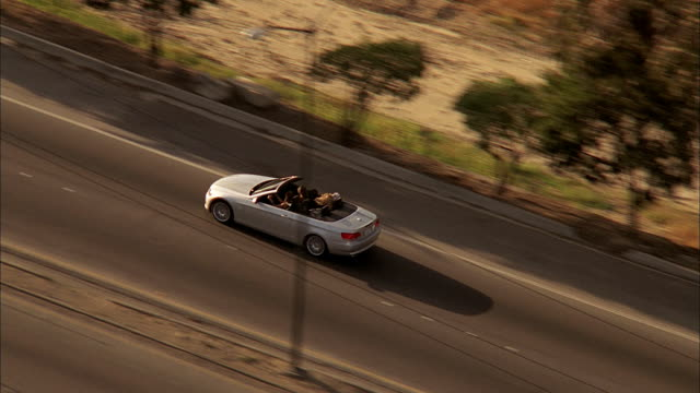 AERIAL Convertible and other traffic driving on freeway