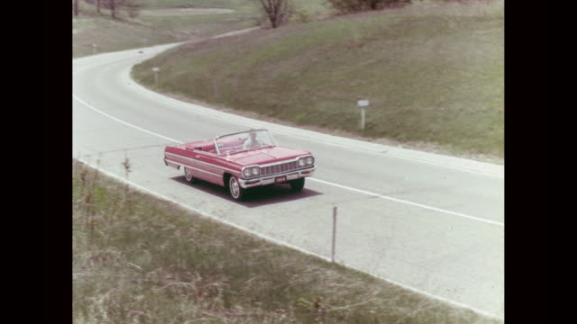 ws pan ha convertible car moving on road / united states - 1964 stock videos and b-roll footage