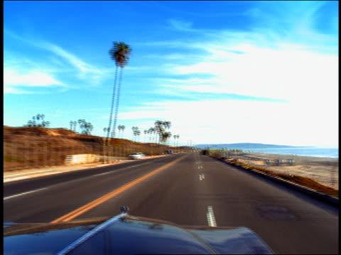 Convertible car point of view pan driving on coastal road / Venice Beach, Los Angeles, California