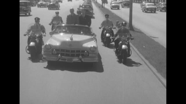 vídeos de stock, filmes e b-roll de convertible carrying dwight eisenhower moves slowly through crowd at airport / motorcade along highway escorted by motorcycle police / motorcade... - dwight eisenhower