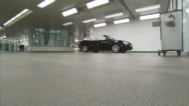 a convertible occupies a solitary position on a showroom floor. - オープンカー点の映像素材/bロール